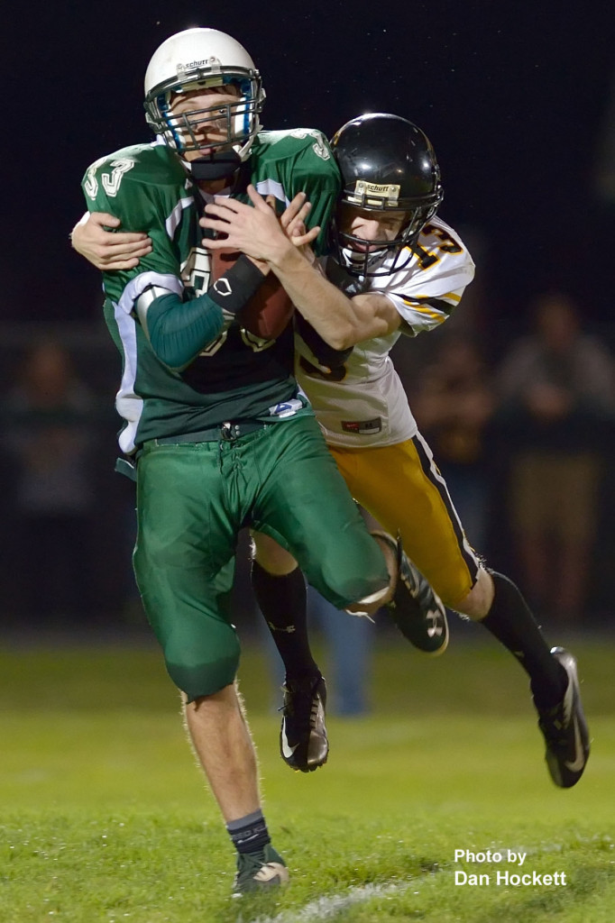 Photo by Dan Hockett West Burlington – Notre Dame Wide Receiver Jarod Fogle catches a pass in front of Louisa – Muscatine Line Backer Ian Barnhart in the second quarter of Friday night's homecoming game in West Burlington. L&M defeated WBND, 72-34.