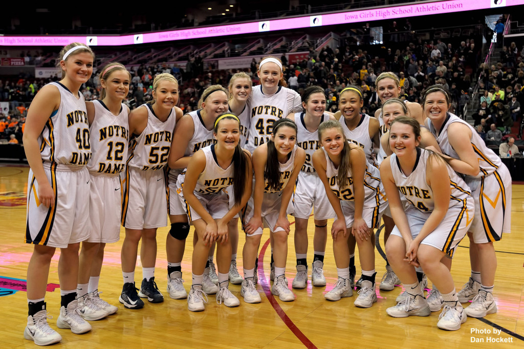 Photo by Dan Hockett Notre Dame Teammates pose to celebrate winning the Class 1A State Quarterfinal over Adair-Casey, 90-50, Monday afternoon at Wells Fargo Arena in Des Moines.