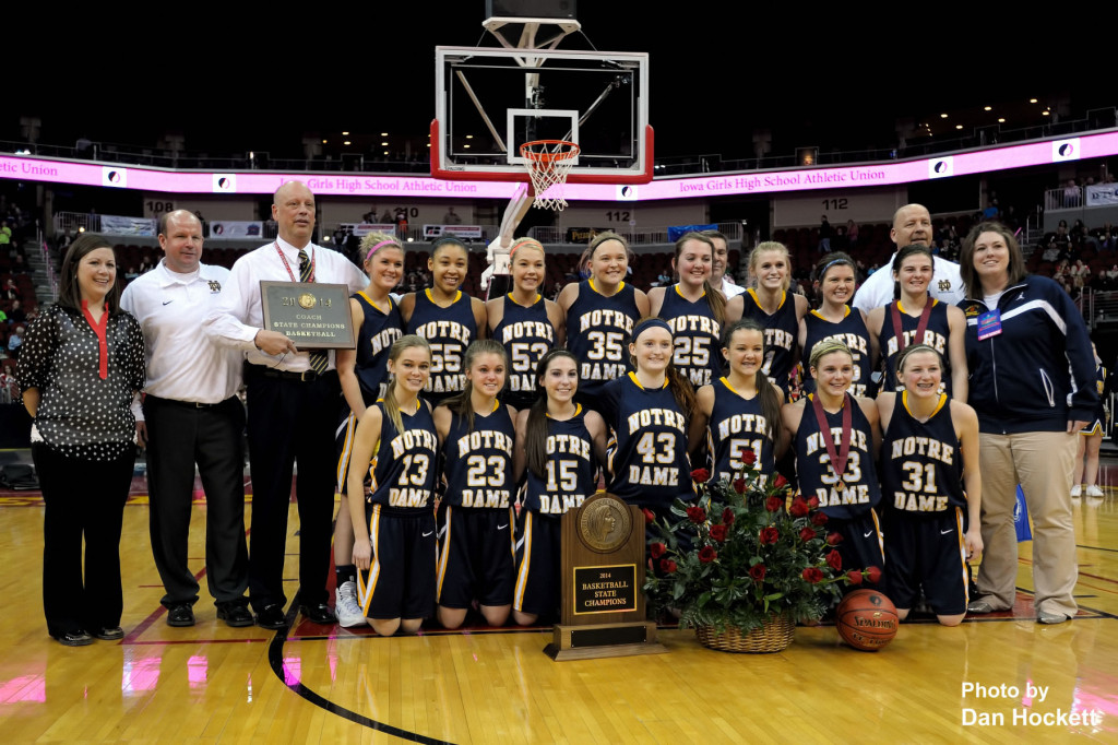 Photo by Dan Hockett Notre Dame Nikes Players and Coaches pose for the official 2014 Class 1A Girls State Champion photo at Well Fargo Arena in Des Moines. Front (l-r): Alex Ackerman, Courtney Abolt, Courtney Coffin, Emily Salvador, Johanna Myers, Taylor Hickey, Gabrielle Koelker. Middle (l-r): Kaitlyn Klein, Dee Dee Gilbert, Reagan Rogerson, Alyssa Schwartz, Jayla Kreiss, Kori Mesecher, Hannah Delaney, Riley Killbride. Back (l-r): Trainer Erin Bush, Asst  Coach Dan Hickey, Head Coach Kollin Alfred, Asst. Coach Steve Gray, Asst. Coach Jim Myers, Asst. Coach Kayla Henry.