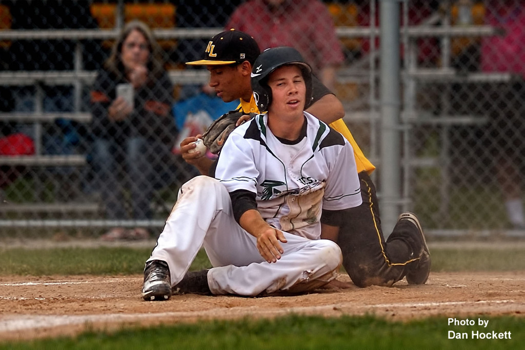 Photo by Dan Hockett West Burlington's Tyson Abbott (foreground) is disappointed after being tagged out at home by New London Pitcher Jayden Flowers Monday night in West Burlington. New London defeated West Burlington, 7-5.