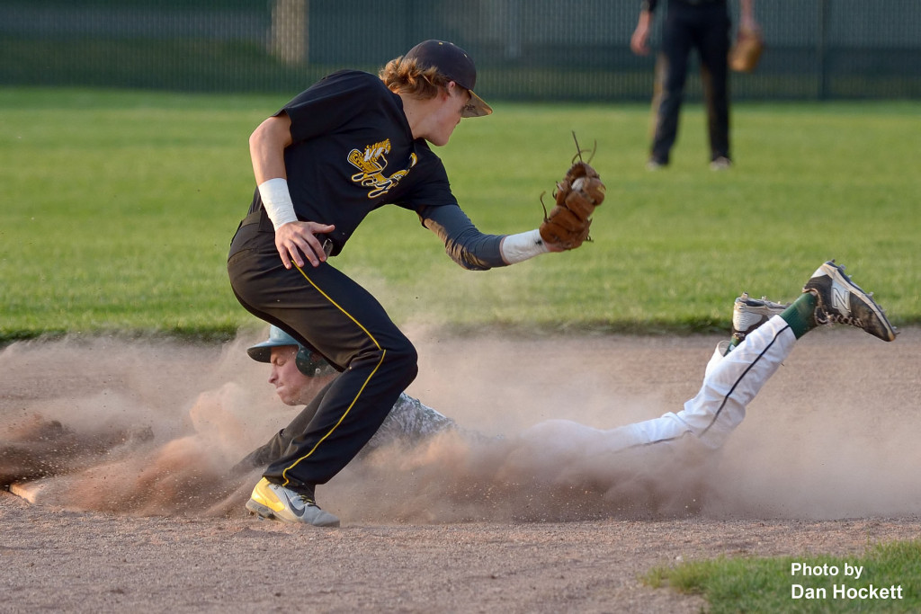 Photo by Dan Hockett West Burlington's Brant Wrede slides safe at second beating the tag from New London Shortstop Jayden Flowers Tuesday night in West Burlington. New London defeated West Burlington, 10-7.