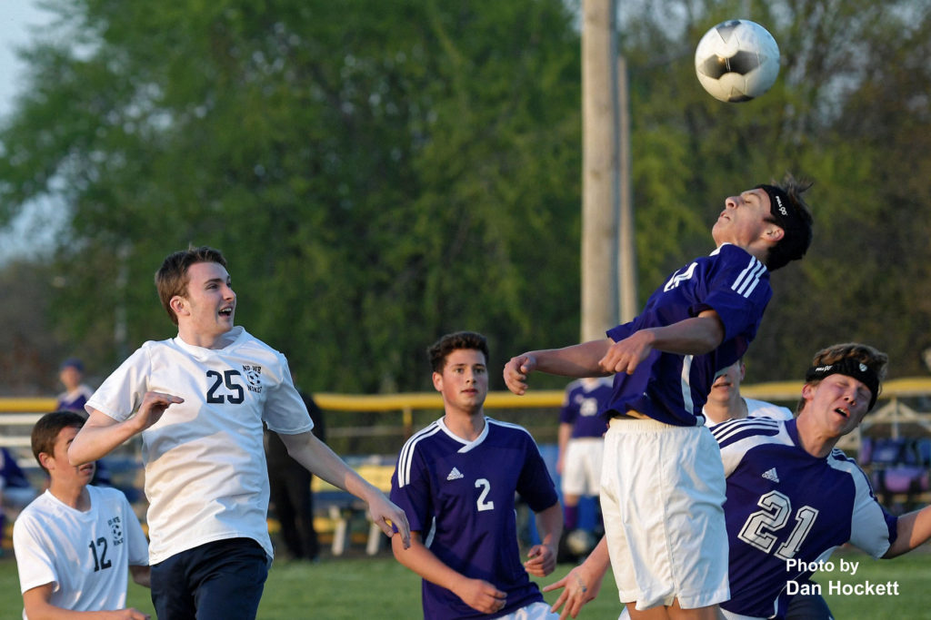 Photo by Dan Hockett Burlington's Brody Ertzinger heads the ball in front of Nikes' Jakob Anderson (25) Friday night at Tackleson Field in Burlington. Burlington defeated Notre Dame – West Burlington, 1-0.