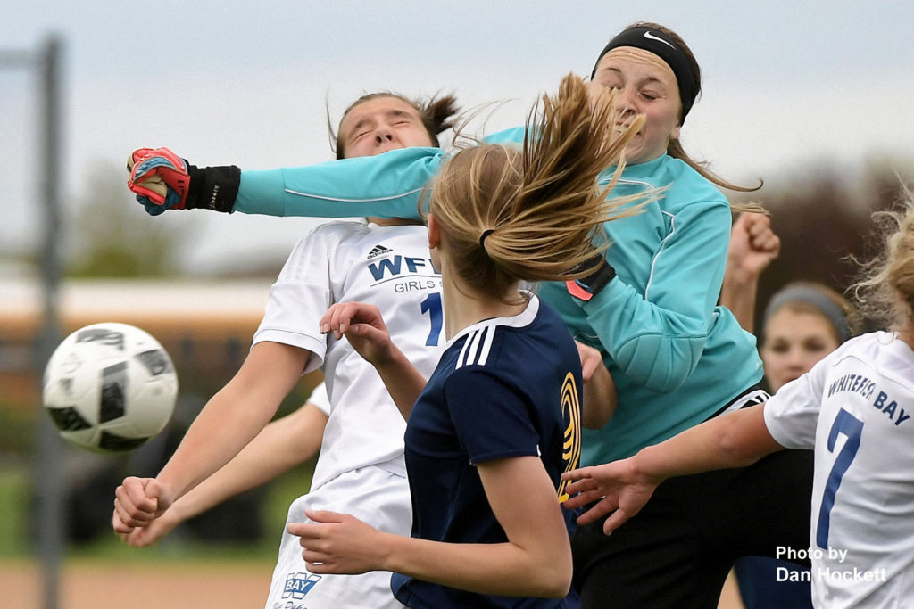 Photo by Dan Hockett Nikes' Goalie Lani Mears punches the ball away from a Whitefish Bay, WI player in the Adidas Tournament of Champions at the Burlington RexPlex Thursday afternoon. Whitefish Bay, WI defeated Notre Dame – West Burlington – Danville, 5-1.