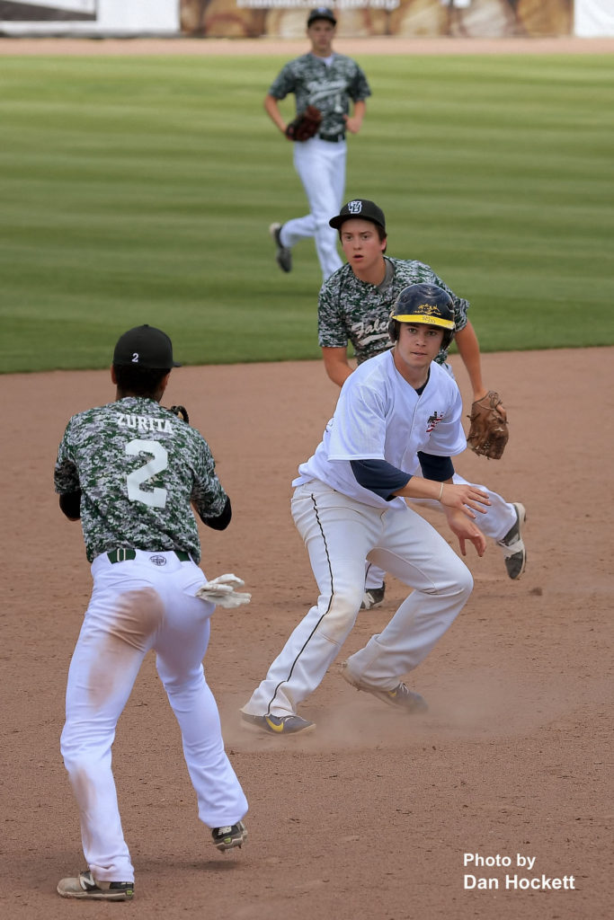 Photo by Dan Hockett Notre Dame's Jack Gray (in white) is run down between second and third by Jayden Zurita (2) in the fifth inning of their game in the Fun City Classic at Community Field in Burlington Saturday. Notre Dame defeated West Burlington, 10-3.