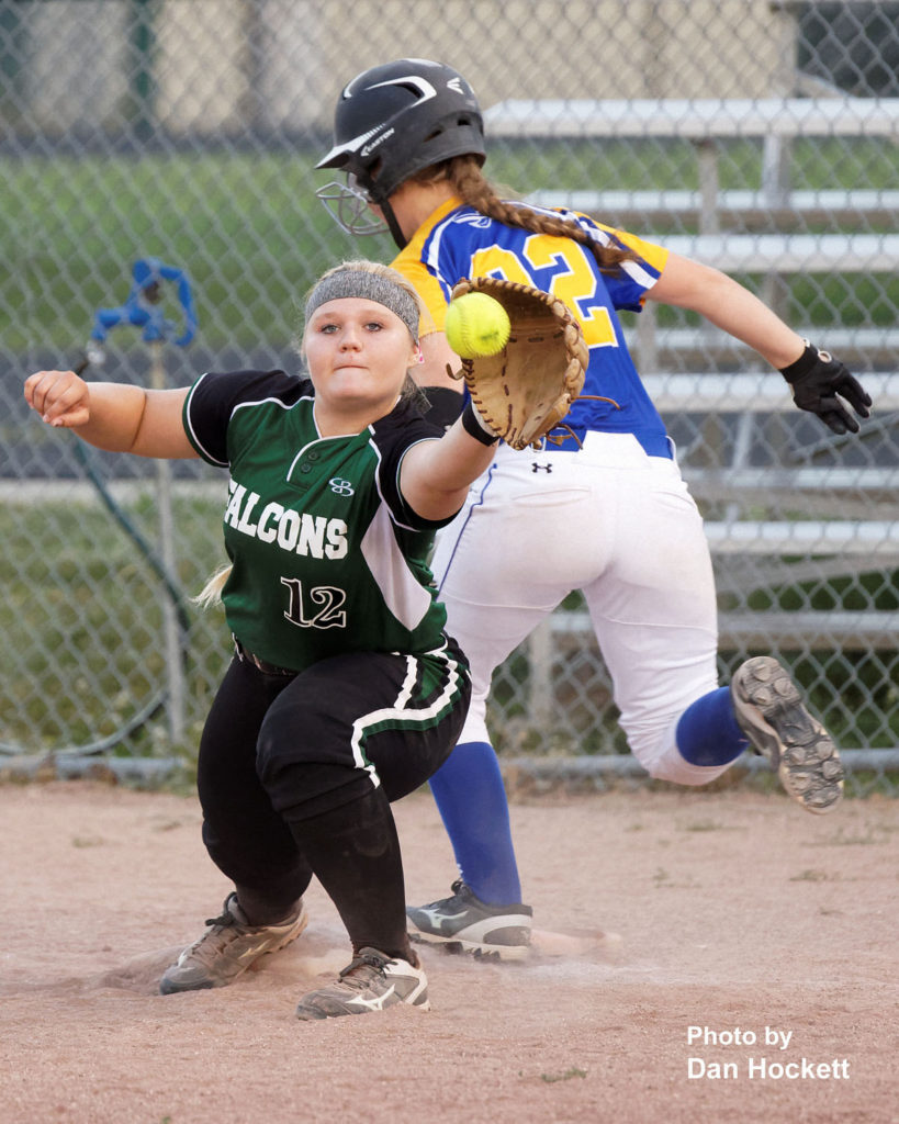 Photo by Dan Hockett A close play at first base in the sixth inning between Wapello's Emma Reid (22) and West Burlington – Notre Dame First Baseman Cassie Powers (12) resulted in Reid being called out Tuesday night in West Burlington. Wapello defeated WBND, 8-1.