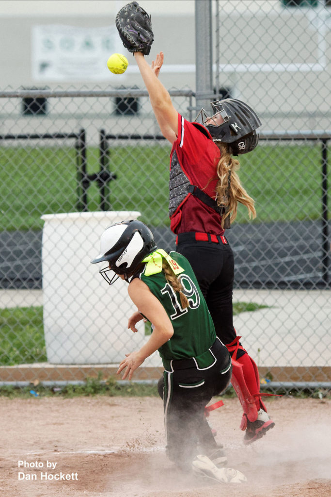 Photo by Dan Hockett West Burlington – Notre Dame's Madelyn Stutsman (19) beats the throw at the plate to Winfield – Mt. Union Catcher Karley Schlee Wednesday night in West Burlington. WBND defeated WMU, 4-2.