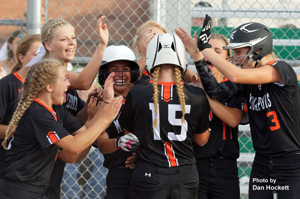 Photo by Dan Hockett Mediapolis' leadoff hitter Mackenzie Petty (15) is congratulated by teammates after starting the game with a solo homerun in first inning against West Burlington – Notre Dame Monday night in West Burlington. Mediapolis defeated West Burlington – Notre Dame, 11-0.
