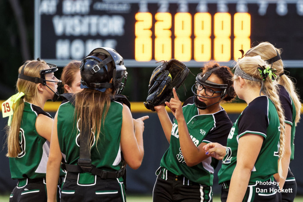 Photo by Dan Hockett West Burlington – Notre Dame Pitcher Olivia Baker (center) meets with her teammates in the seventh inning of the Region-4 Semifinal against Davenport Assumption Friday night in Davenport. Assumption defeated WBND, 7-0.