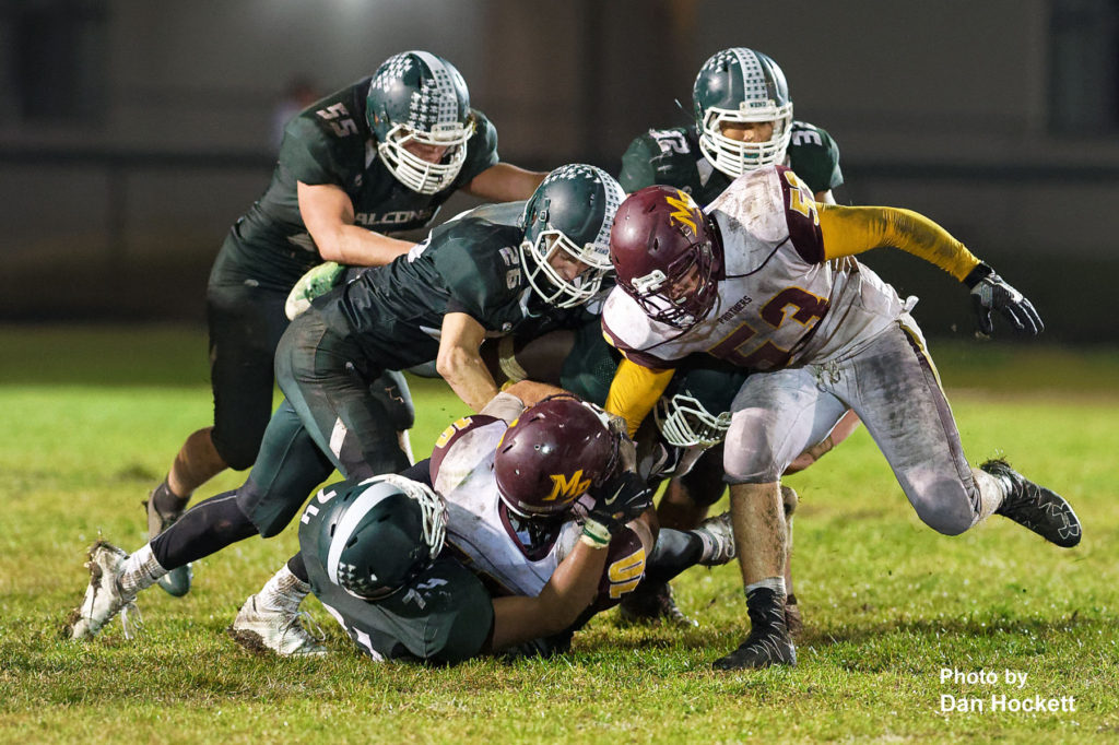 Photo by Dan Hockett West Burlington –Notre Dame's Landen Greer (74), Tanner Snodgrass (26), Luke Shipley (55), Rodrigo Ramos (32), and Shavontae Nelson (under pile) tackle Mt. Pleasant Running Back Pat Canby (10) Friday night in West Burlington. Mt. Pleasant defeated WBND, 21-14.