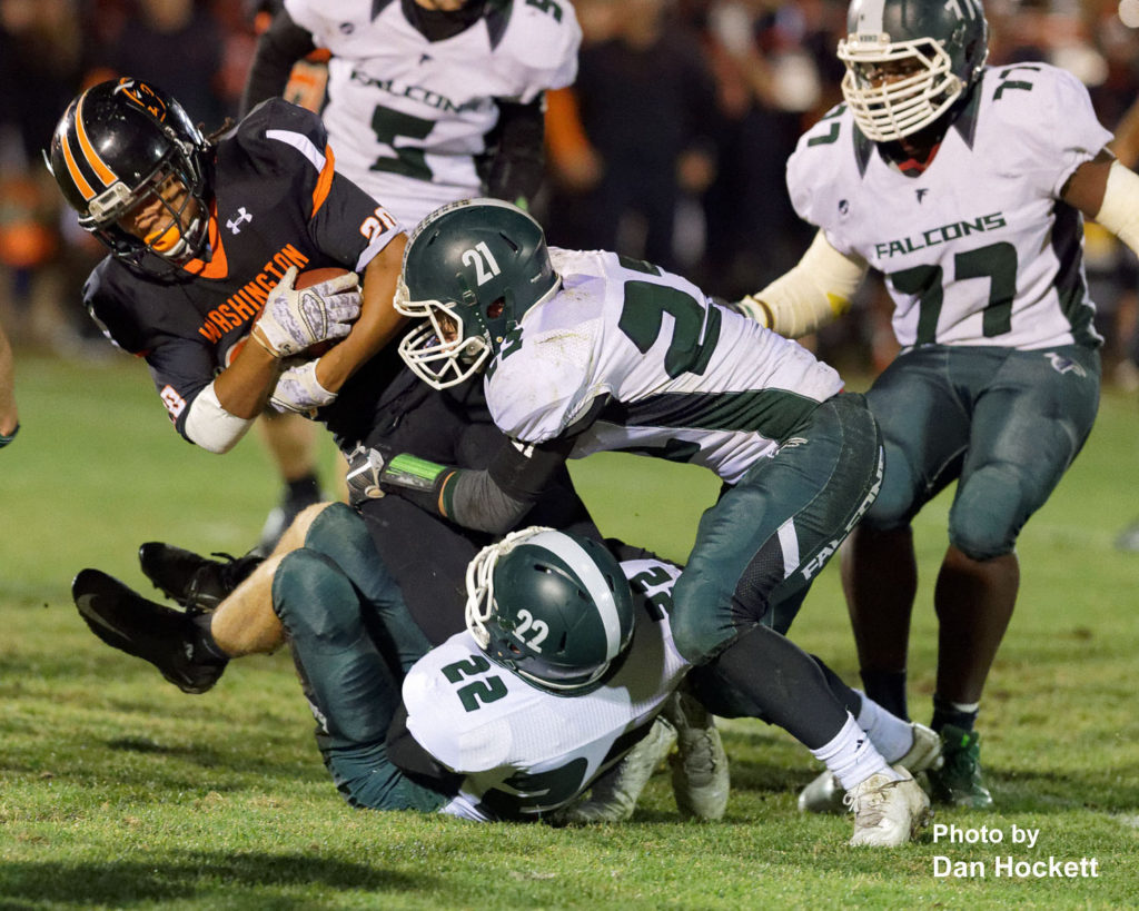 Photo by Dan Hockett West Burlington – Notre Dame's Colten Hohenthaner (22) and Jett Tjaden (21) tackle Washington Running Back Tristin Westphal-Edwards (20) Friday night in Washington. Washington defeated West Burlington – Notre Dame, 49-7.
