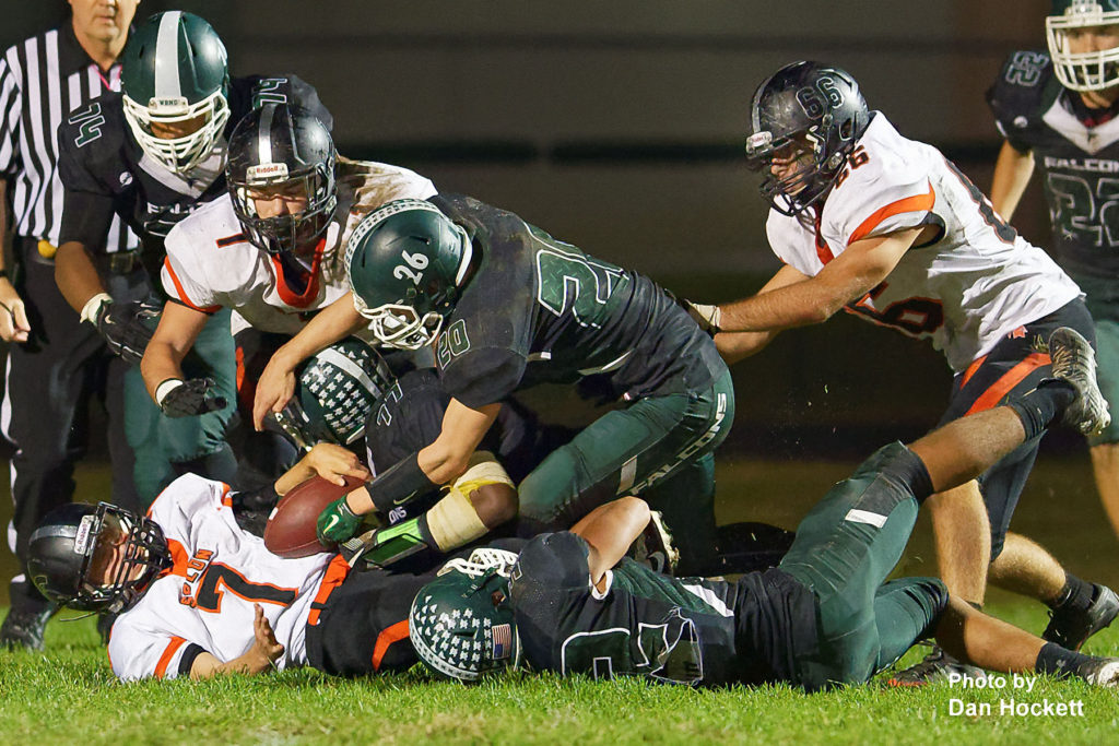 Photo by Dan Hockett West Burlington – Notre Dame's Tanner Snodgrass (20/26), Shavontae Nelson (77), and Colten Hohenthaner (22) tackle then try to strip the ball from Solon Running Back Bryce West (7) Friday night in West Burlington. No. 8 Solon defeated WBND, 42-0.